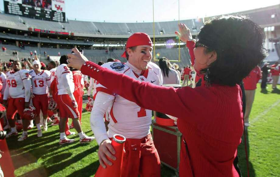 University of Houston quarterback Case Keenum (7) gets a hug from University president Renu Khator, PhD after the Cougars won the  Ticket City Bowl Monday, Jan. 2, 2012, in the Cotton Bowl Stadium in Dallas. Photo: Nick De La Torre, Houston Chronicle / © 2012  Houston Chronicle