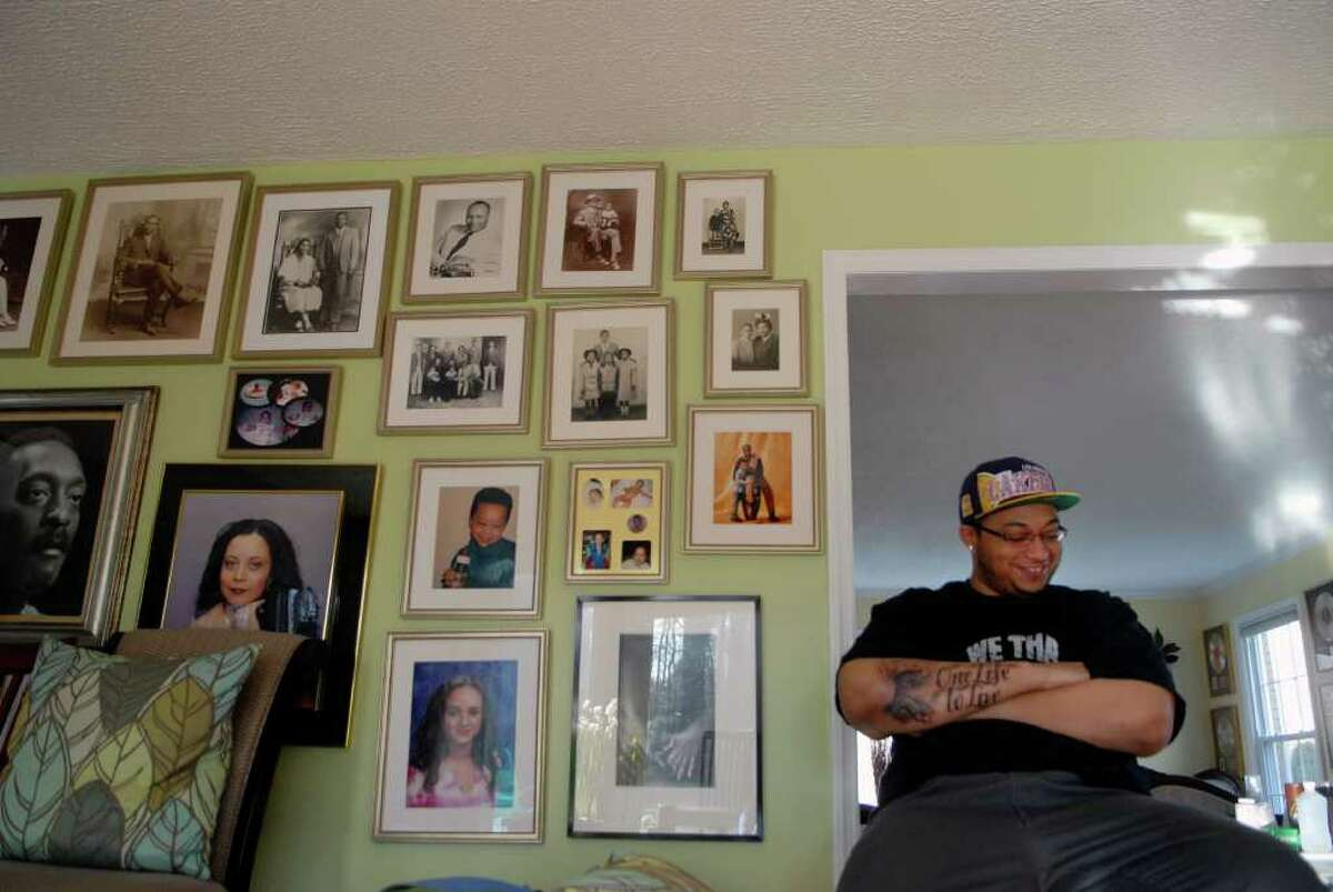 Atiba MacDonald (22), the son of Ralph MacDonald a Stamford musician who recently passed away, sits by a wall of family photos in their Stamford, Conn. home on Thursday December 29, 2011.