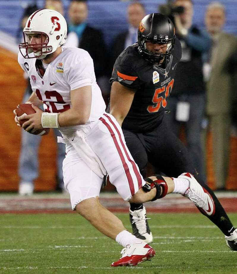 Stanford quarterback Andrew Luck (12) scrambles as Oklahoma State defensive end Jamie Blatnick pursues during the first half of the Fiesta Bowl NCAA college football game Monday, Jan. 2, 2012, in Glendale, Ariz. Photo: AP