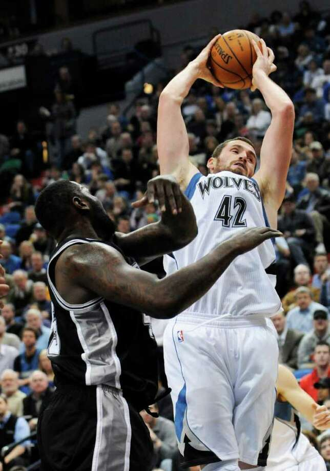 Minnesota Timberwolves' Kevin Love, right, beats San Antonio Spurs' DeJuan Blair to the rebound in the second half of an NBA basketball game, Monday, Jan. 2, 2012, in Minneapolis. The Timberwolves won 106-96. Love led the Timberwolves with 24 points and 15 rebounds. Photo: AP