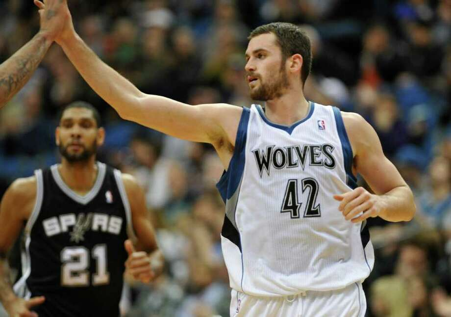 Minnesota Timberwolves' Kevin Love gets a high-five after a basket in the second half of an NBA basketball game, Monday, Jan. 2, 2012, in Minneapolis. Love scored 24 points and had 15 rebounds in the Timberwolves' 106-96 win. At left is Spurs' Tim Duncan. (AP Photo/Jim Mone) Photo: Associated Press