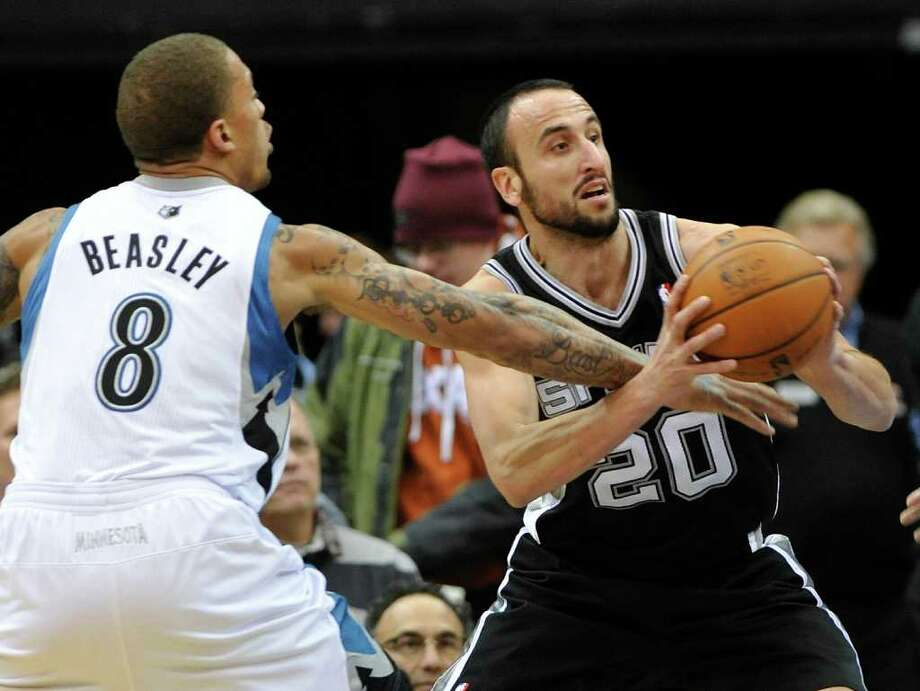 Minnesota Timberwolves' Michael Beasley, left, tries to knock the ball away from San Antonio Spurs' Manu Ginobili, of Argentina, in the first half of an NBA basketball game, Monday, Jan. 2, 2012, in Minneapolis. (AP Photo/Jim Mone) Photo: Associated Press