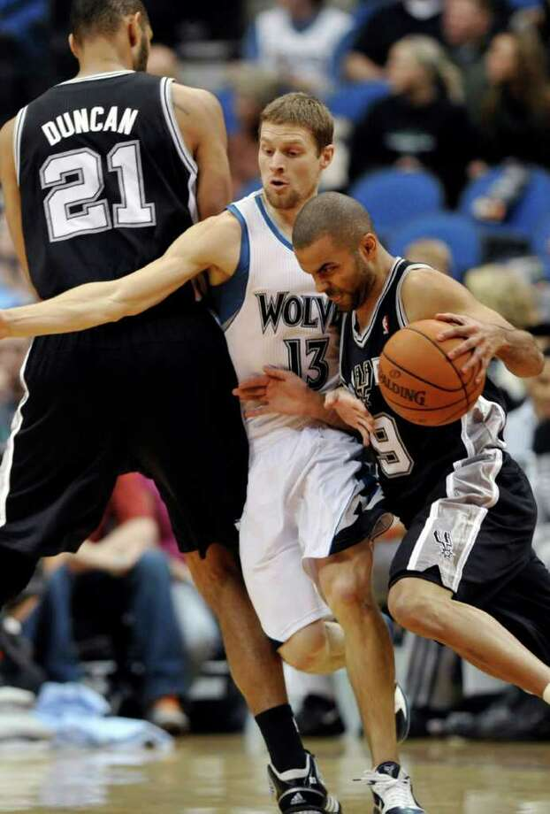 Minnesota Timberwolves' Luke Ridnour, center, gets pinned in by San Antonio Spurs' Tim Duncan , left, and teammate Tony Parker as Parker drives by in the first half of an NBA basketball game, Monday, Jan. 2, 2012, in Minneapolis. (AP Photo/Jim Mone) Photo: Associated Press