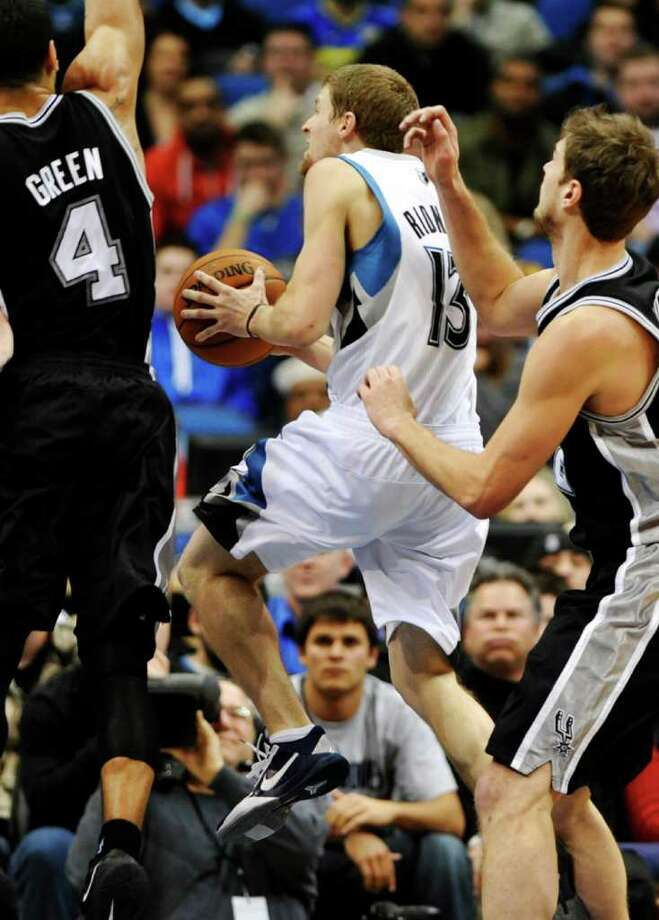 San Antonio Spurs' Daniel Green, left, and Tiago Splitter, right, of Brazil, defend as Minnesota Timberwolves' Luke Ridnour lays up in the second half of an NBA basketball game, Monday, Jan. 2, 2012, in Minneapolis. The Wolves won 106-96. Ridnour scored 19 points with nine assists. (AP Photo/Jim Mone) Photo: Associated Press