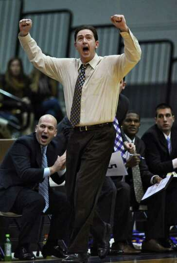 UAlbany men's basketball coach Will Brown celebrates a score by his players during the first half of