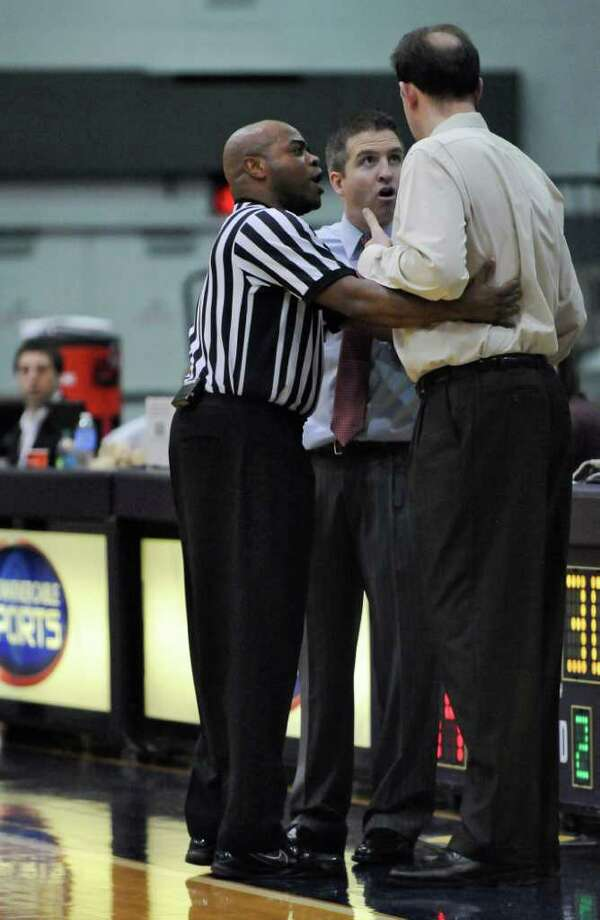 Official Jeffrey Anderson, left,  keeps UAlbany men's basketball coach Will Brown, right, and Hartford coach John Gallagher, center, separated as he tries to calm the two men after a UAlbany player sustained a hard foul, during the second half of their 88-63 victory over Hartford at SEFCU Arena on Monday Jan. 2, 2012 in Albany, N.Y.  (Philip Kamrass / Times Union ) Photo: Philip Kamrass / 00015593A
