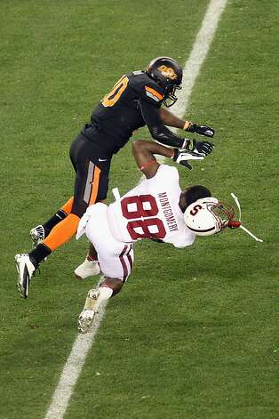 GLENDALE, AZ - JANUARY 02:  Ty Montgomery #88 of the Stanford Cardinal holds onto the ball for a reception but loses is helmet as he is tackled by Markelle Martin #10 of the Oklahoma State Cowboys during the Tostitos Fiesta Bowl on January 2, 2012 at University of Phoenix Stadium in Glendale, Arizona.  (Photo by Christian Petersen/Getty Images) Photo: Christian Petersen, Getty Images
