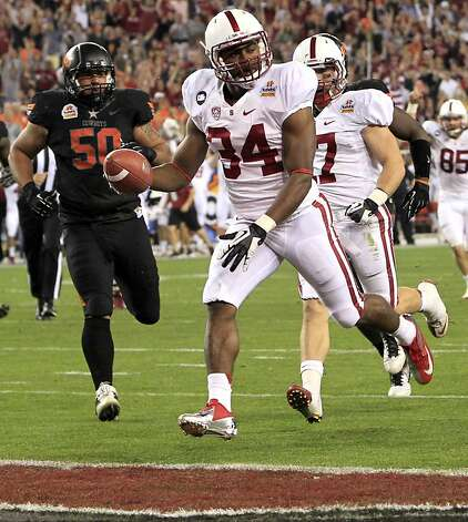 Stanford running back Jeremy Stewart (34) scores a touchdown as Oklahoma State defensive end Jamie Blatnick (50) pursues during the first half of the Fiesta Bowl NCAA college football game Monday, Jan. 2, 2012, in Glendale, Ariz. (AP Photo/Ross D. Franklin) Photo: Ross D. Franklin, Associated Press