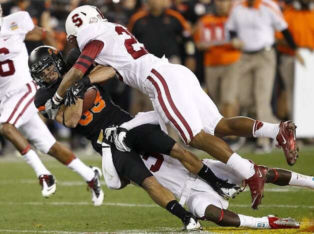 Oklahoma State wide receiver Colton Chelf, left, is tackled by Stanford safety Delano Howell, right, during the first half of the Fiesta Bowl NCAA college football game Monday, Jan. 2, 2012, in Glendale, Ariz. (AP Photo/Matt York) Photo: Matt York, Associated Press