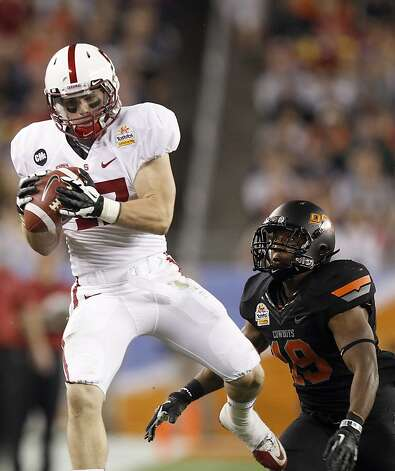 Stanford wide receiver Griff Whalen, left, makes a reception in front of Oklahoma State cornerback Brodrick Brown, right, to set up a Stanford touchdown during the first half of the Fiesta Bowl NCAA college football game Monday, Jan. 2, 2012, in Glendale, Ariz. (AP Photo/Paul Connors) Photo: Paul Connors, Associated Press