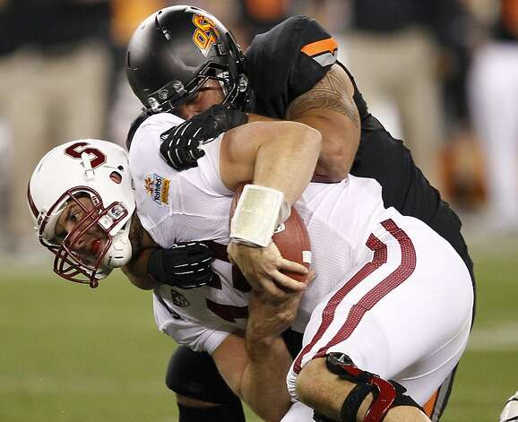 Stanford quarterback Andrew Luck, front, is sacked by Oklahoma State defensive end Jamie Blatnick during the second half of the Fiesta Bowl NCAA college football game Monday, Jan. 2, 2012, in Glendale, Ariz. (AP Photo/Matt York) Photo: Matt York, Associated Press