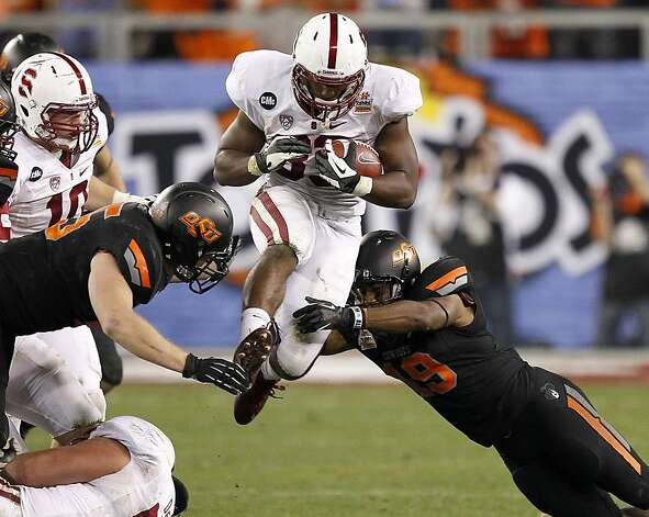 Stanford running back Stepfan Taylor, center, is tackled by Oklahoma State cornerback Brodrick Brown, right, and linebacker Caleb Lavey, left, during the second half of the Fiesta Bowl NCAA college football game Monday, Jan. 2, 2012, in Glendale, Ariz. (AP Photo/Matt York) Photo: Matt York, Associated Press