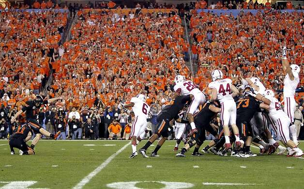 Oklahoma State kicker Quinn Sharp (13) kicks the game-winning field goal as teammate Wes Harlan (11) holds against Stanford during overtime of the Fiesta Bowl NCAA college football game, Monday, Jan. 2, 2012, in Glendale, Ariz. Oklahoma State won 41-38. (AP Photo/Matt York) Photo: Matt York, Associated Press