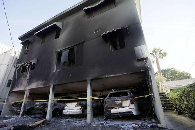 "The charred remains of cars are seen in a burned Los Angeles apartment building carport Monday, Jan 2, 2012.  Twelve more suspected arson fires broke out early Monday in the Los Angeles area, and a ""person of interest"" was taken into custody for questioning in connection with the dozens of suspicious car fires that have hit the city since last week. (AP Photo/Nick Ut) Photo: Nick Ut, Associated Press"