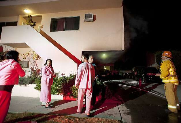 Residents stand outside of their apartment after a car fire in a carport forced their evacuation in the Sherman Oaks neighborhood of Los Angeles on Monday, Jan. 2, 2012. For the fifth night in a row, a spate of arson fires has sent firefighters scrambling to extinguish car fires in the Hollywood, Hollywood Hills, Studio City, and Sherman Oaks neighborhoods of Los Angeles. The Los Angeles Fire Department confirms a person of interest has been detained and is being questioned in connection with the arson spree. (AP Photo/Dan Steinberg) Photo: Dan Steinberg, Associated Press