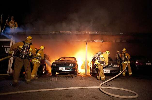 Los Angeles Fire Department firefighters extinguishes numerous cars on fire in a carport in the Sherman Oaks neighborhood of Los Angeles on Monday, Jan. 2, 2012. For the fifth night in a row, a spate of arson fires has sent firefighters scrambling to extinguish car fires in the Hollywood, Hollywood Hills, Studio City, and Sherman Oaks neighborhoods of Los Angeles. The Los Angeles Fire Department confirms a person of interest has been detained and is being questioned in connection with the arson spree. (AP Photo/Dan Steinberg) Photo: Dan Steinberg, Associated Press