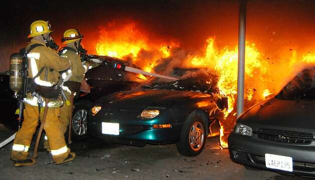 "Los Angeles firefighters battle an arson car fire under a carport in Los Angeles Monday, Jan. 2, 2012.  Twelve suspected arson fires broke out early Monday in the Los Angeles area. A ""person of interest"" was taken into custody for questioning in connection with the dozens of suspicious car fires that have hit the city during the past  week. (AP Photo/Mike Meadows) Photo: Mike Meadows, Associated Press"