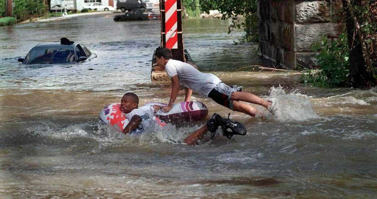 Michael McCrea, 17, left and Santos Figueroa, 16, swim with inflatable tubes in the flooded waters under the West St. bridge in Danbury following Hurricane Floyd in September 1999.