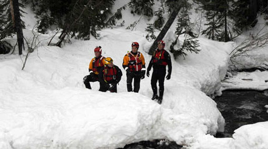 In this pool photo provided  by the Pierce Co. Sheriff's Deptartment, members of the Pierce County  Swiftwater Rescue Team stand alongside the creek, Monday  near the spot where they recovered the body of Benjamin Colton Barnes,  who allegedly shot and killed a park ranger Sunday during a traffic stop  in the park. (AP Photo/Pierce Co. Sheriff's Dept., Ed Troyer)