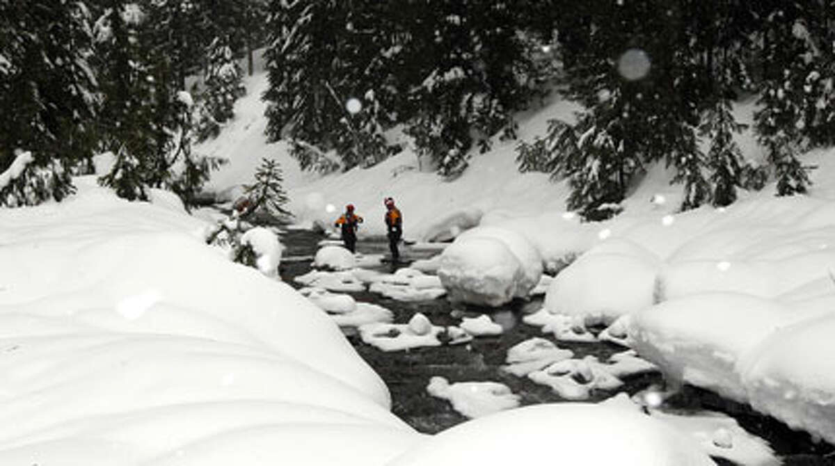 In this pool photo provided by the Pierce County Sheriff's Deptartment, members of the Pierce County Swiftwater Rescue Team stand in a creek at Mount Rainier National Park in Washington state, at the spot where a gun carried by Benjamin Colton Barnes, who allegedly shot and killed a park ranger Sunday during a traffic stop in the park, was recovered after Barnes' body was found further down in the creek, Monday. (AP Photo/Pierce Co. Sheriff's Dept., Ed Troyer)