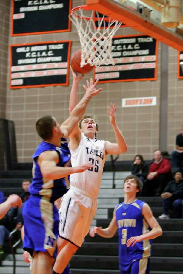 Staples' Mike Argosh attempts a layup against Newtown in the consolation game of the Ridgefield Holiday Tournament. Argosh had 18 points in the 65-56 victory and was named to the All-Tournament team. Photo: Elaine Rankowitz / Contributed P