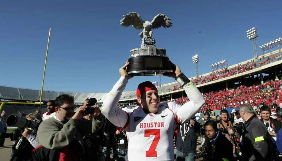 University of Houston quarterback Case Keenum (7) walks off the field with the Ticket City Bowl trophy after beating Penn State 30-14 Monday, Jan. 2, 2012, in the Cotton Bowl Stadium in Dallas. Photo: Nick De La Torre, Houston Chronicle / © 2012  Houston Chronicle