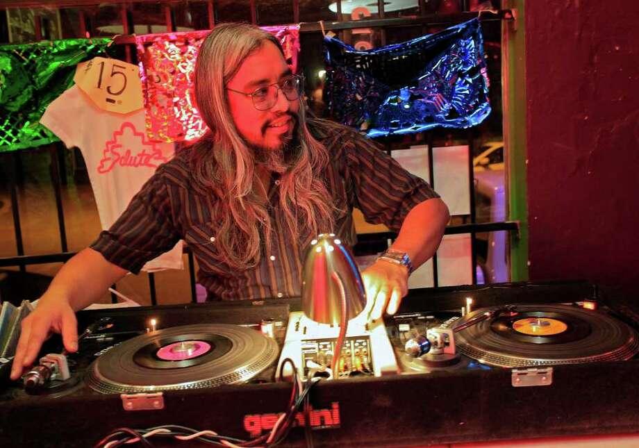 Eddie Hernandez, known as DJ Plata, spins the records at Saluté International Bar. Photo: J. MICHAEL SHORT, FOR THE EXPRESS-NEWS / THE SAN ANTONIO EXPRESS-NEWS