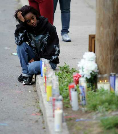 Tyasia Hogan, the girlfriend of Eddie Stanley, sits by a makeshift memorial for Stanley on Bridge Street in Schenectady, on Monday June 13, 2011, near where Stanley was fatally shot the day before.  (Skip Dickstein/ Times Union archive) Photo: Skip Dickstein / 00013514A