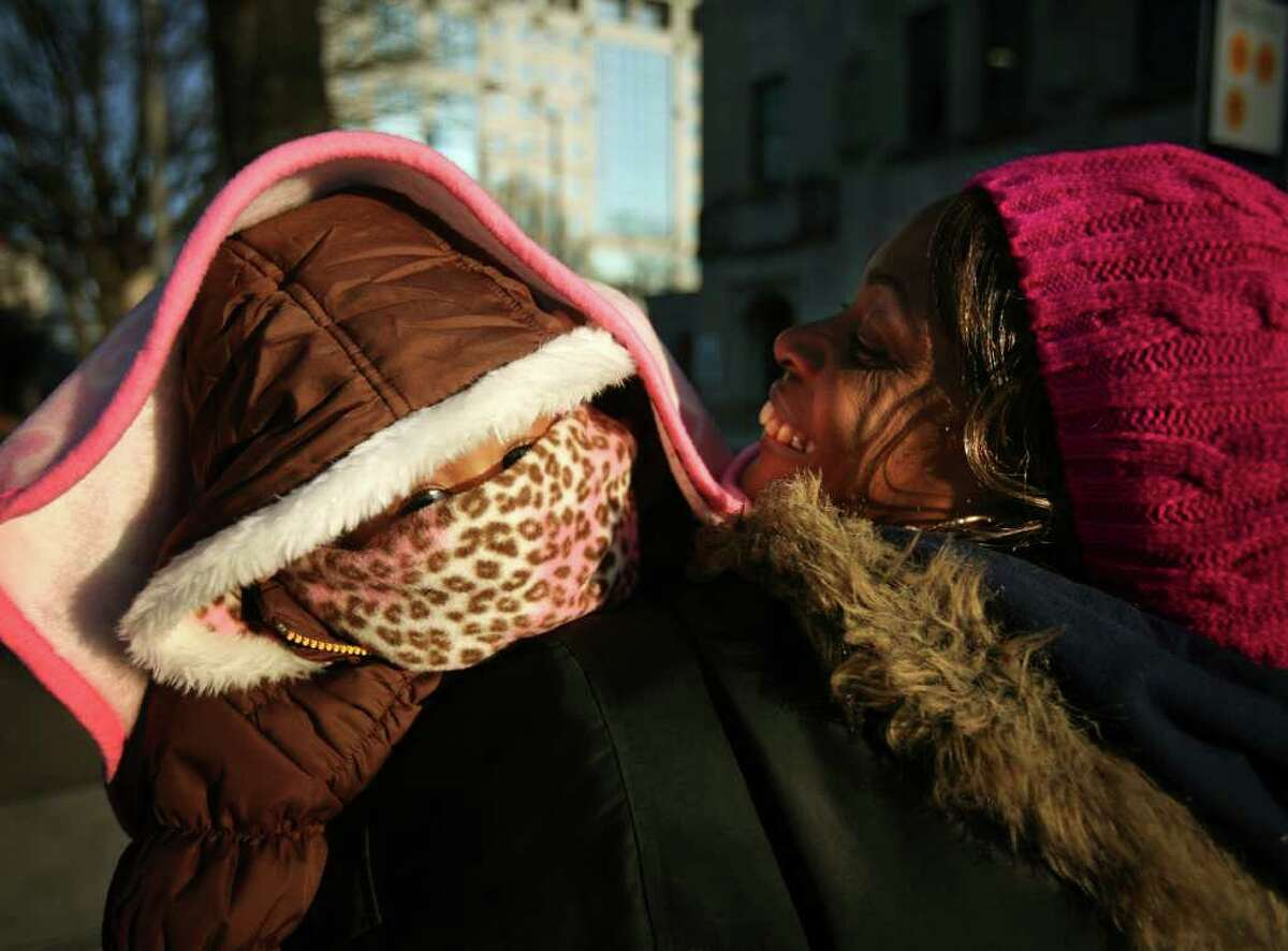 Angela Brown of Bridgeport holds Angelique, 1, covered except for her eyes as they wait for a public bus on John Street in Bridgeport on Tuesday, January 3, 2012.