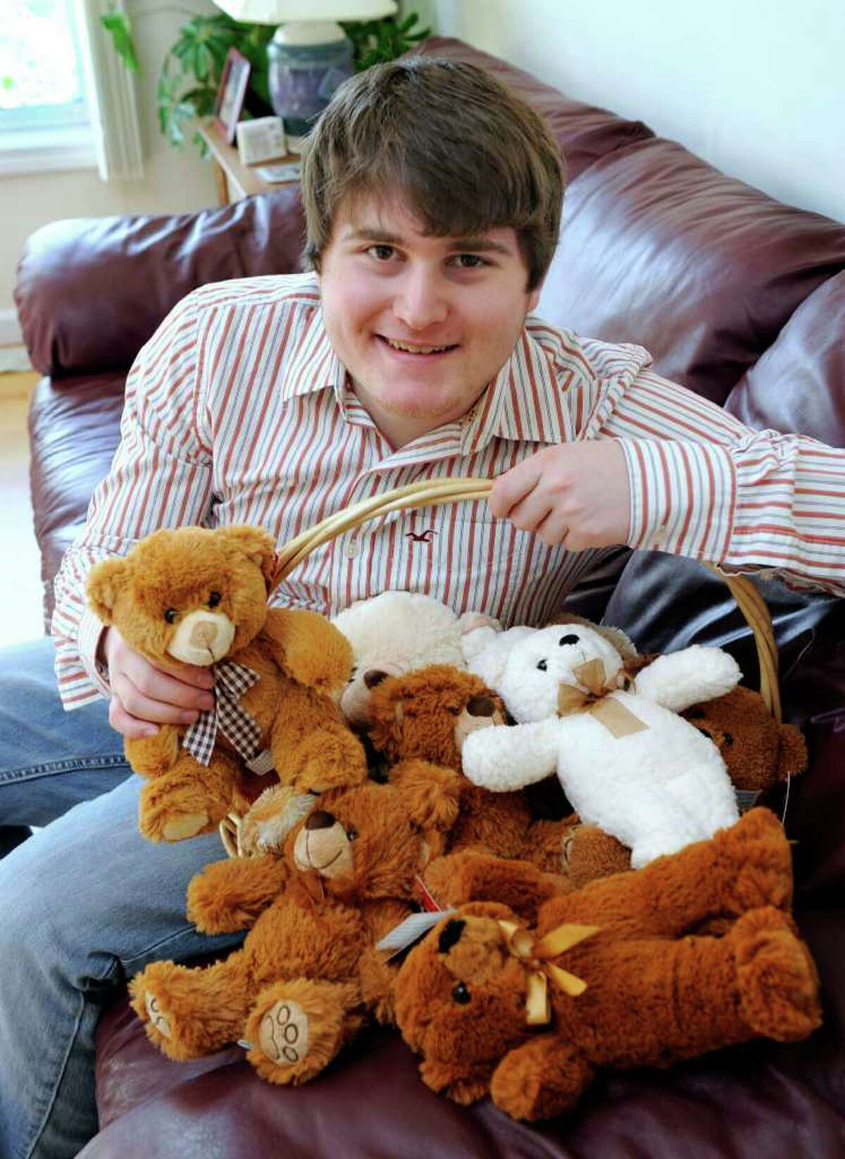 Adam Schecter, 18, of Ridgefield, poses with some the stuffed animals that he purchased with money he raises from can and bottle drives. Photo taken Friday, Dec. 30, 2011.