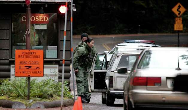 Armed U.S. Park police check cars approaching the Nisqually entrance to Mount Rainier National Park, allowing only park employees entrance Tuesday morning, Jan. 3, 2012, near Ashford, Wash. The park remained closed while the investigation continued a day after searchers found the body of the gunman suspected of shooting and killing Ranger Margaret Anderson on Sunday. Benjamin Colton Barnes was lying partially submerged in a frigid mountain creek with snow banks standing several feet high on each side. Photo: Elaine Thompson, AP / AP