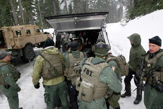 In this photo provided by the Pierce Co. Sheriff's Dept., FBI SWAT team members load the body of Benjamin Colton Barnes into a vehicle Monday, Jan. 2, 2012, at Mount Rainier National Park in Washington state. Barnes' body was recovered from a creek bed Monday, after he allegedly shot and killed a park ranger Sunday during a traffic stop in the park. Barnes did not have any external wounds and appears to have died due to the elements, Sheriff's spokesman Ed Troyer said. (AP Photo/Pierce Co. Sheriff's Dept., Ed Troyer, Pool) Photo: Ed Troyer, ASSOCIATED PRESS / AP2012
