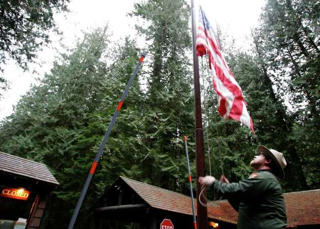 Park Ranger Matt Chalup lowers the flag to half-staff at an entrance to Mount Rainier National Park in Washington state, Monday, Jan. 2, 2012, the day after Park Ranger Margaret Anderson was killed by a gunman inside the park. The park remains closed Monday as officials search for the gunman, who remained at-large after he fled on foot. (AP Photo/Ted S. Warren) Photo: Ted S. Warren, ASSOCIATED PRESS / AP2012