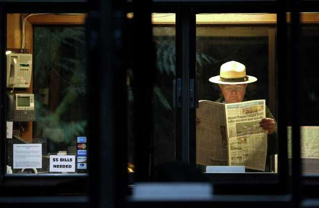 Park Ranger Ralph Davis reads a copy of the (Tacoma) News Tribune, Tuesday, Jan. 2, 2012, as he staffs an entrance booth to Mount Rainier National Park, the day after Park Ranger Margaret Anderson was killed by a gunman inside the park. The park remained closed Tuesday as officials searched for the gunman, who remained at-large after he fled on foot. Photo: Ted S. Warren, AP / AP