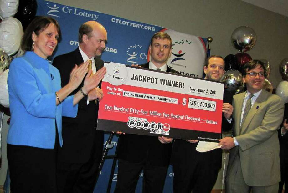 Greenwich wealth managers Tim Davidson, second left, Greg Skidmore, center, and Brandon Lacoff, second right, claimed a $254.2 million Powerball jackpot Nov. 28. Lottery officials are gambling that people are willing to pay more for the hope of becoming a millionaire in a down economy. (AP Photo/Connecticut Lottery, HO) Photo: Associated Press / Connecticut Lottery