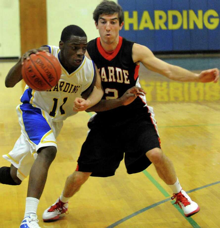 Harding's #11 Steven Walker, left, tries to get past Fairfield Warde's Matthew McTague, during boys basketball action in Bridgeport, Conn. on Tuesday January 3, 2011. Photo: Christian Abraham / Connecticut Post