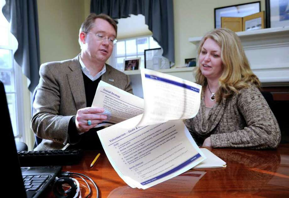 Michael Johnston, 51, left, outgoing CEO of The United Way of Western Connecticut, meets in his office with Kim Morgan, 44, who will replace him on an interim basis. Photo taken Tuesday, Jan. 3, 2012. Photo: Carol Kaliff / The News-Times
