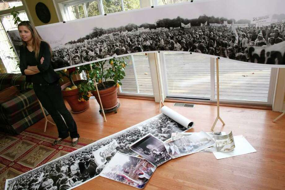 Greenwich resident and Harvard student Olenka Polak talks about the exhibition she helped organize at the university of her father's photographs documenting the Solidarity movement in Soviet Poland.  She stands in her Riverside home with one of her father's panoramic photos Friday, Dec. 30, 2011. Photo: DAVID AMES, ST / GREENWICH TIME