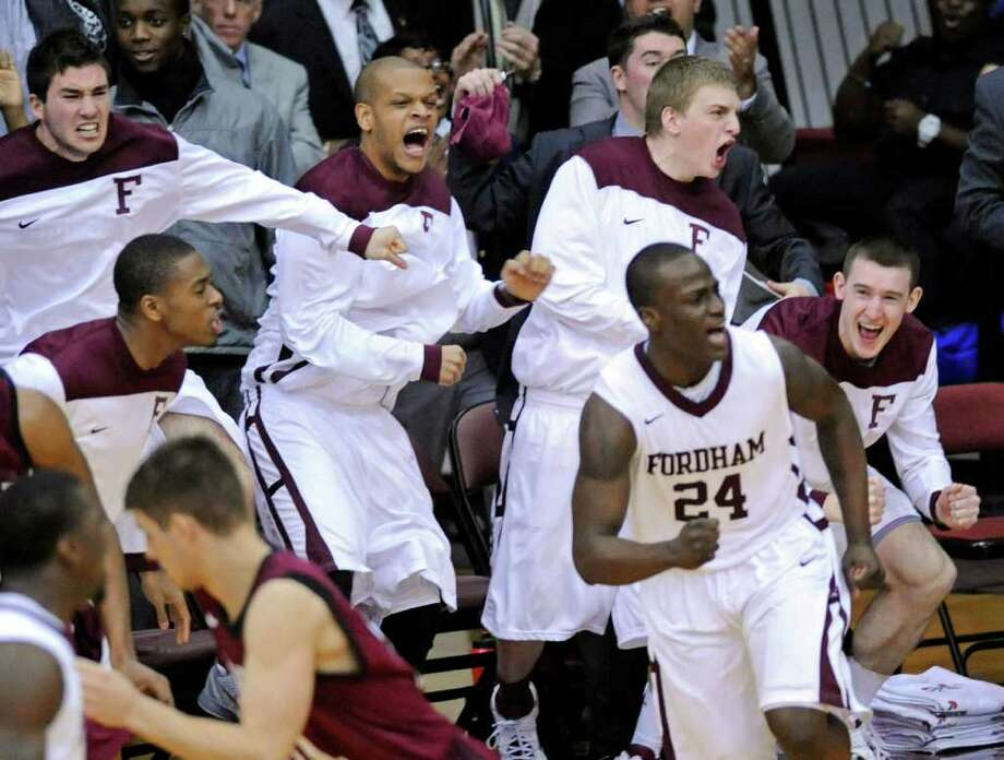Fordham players celebrate after Bryan Smith (center) hit a 3-point shot during the Rams' upset of No. 22 Harvard. Photo: BILL KOSTROUN, ASSOCIATED PRESS