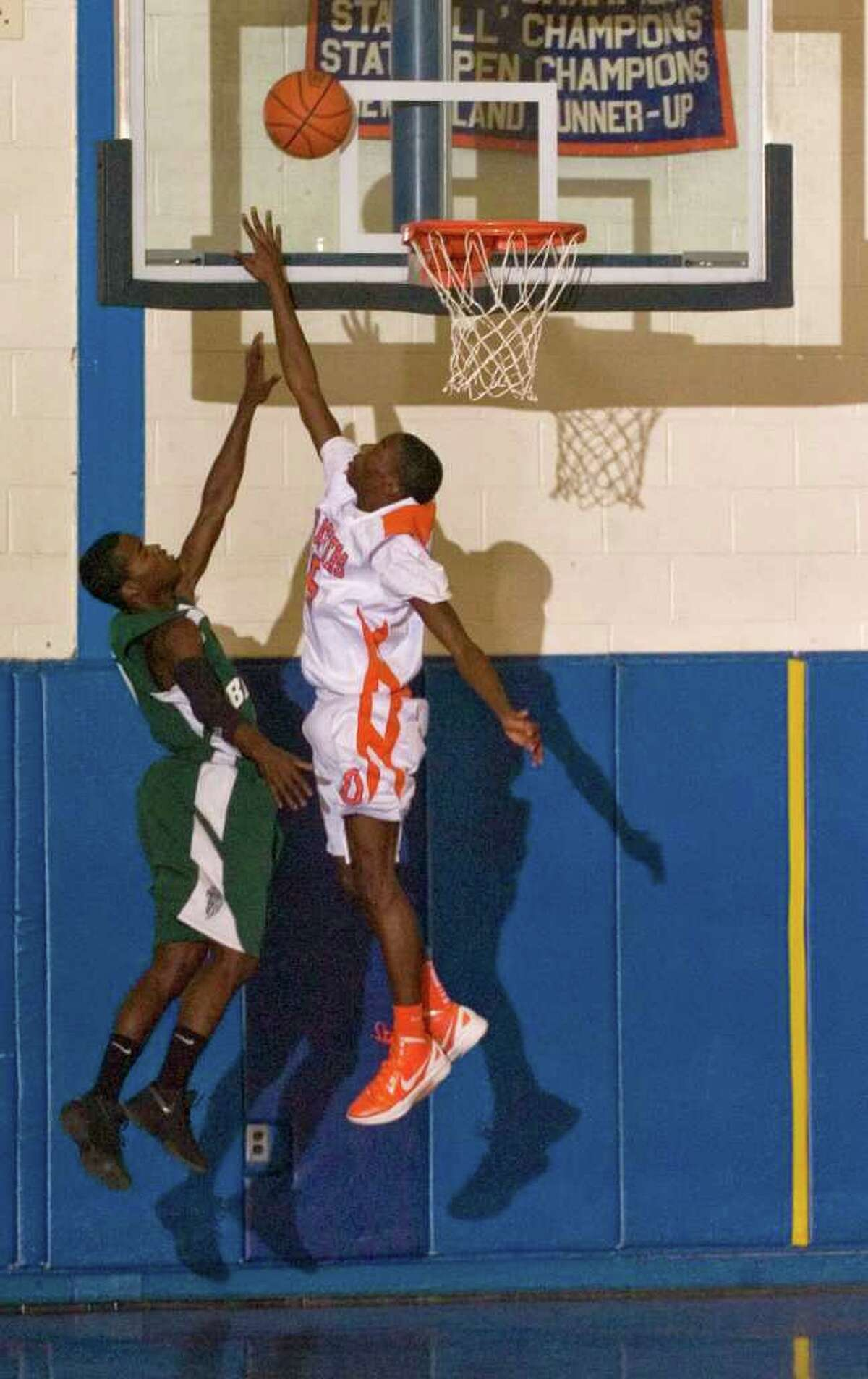 Bassick's Jerond Rogers shoots over Danbury's C.J. White during their game at Danbury High School on Tuesday, Jan. 3, 2012. Danbury won 86-85 in overtime.