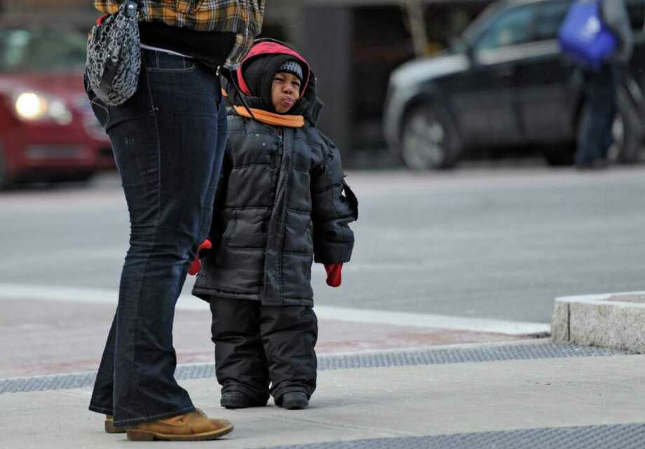 A toddler is all bundled up to stay warm and protected from the cold winds on lower State Street in Albany, N.Y. Jan 3, 2012. (Skip Dickstein / Times Union) Photo: SKIP DICKSTEIN / 2011