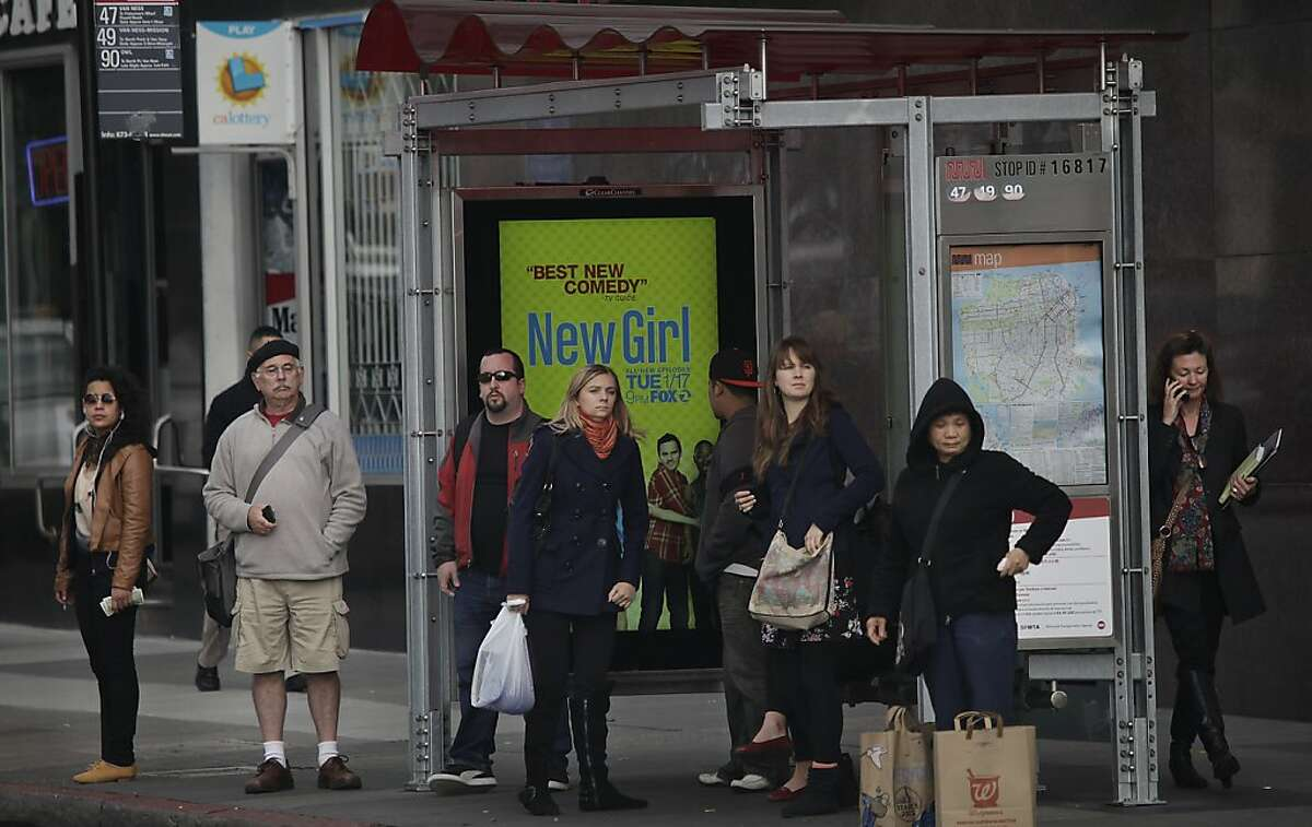 People wait at a bus stop on Van Ness Avenue at Market Street for the arrival of a bus on Tuesday, January 3, 2012 in San Francisco, Calif.