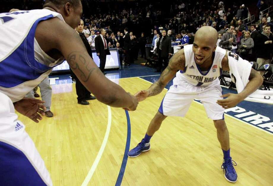 Seton Hall guard Jordan Theodore, right, and teammate Herb Pope celebrate after beating Connecticut 75-63 during an NCAA college basketball game, Tuesday, Jan. 3, 2012, in Newark, N.J. (AP Photo/Julio Cortez) Photo: Julio Cortez