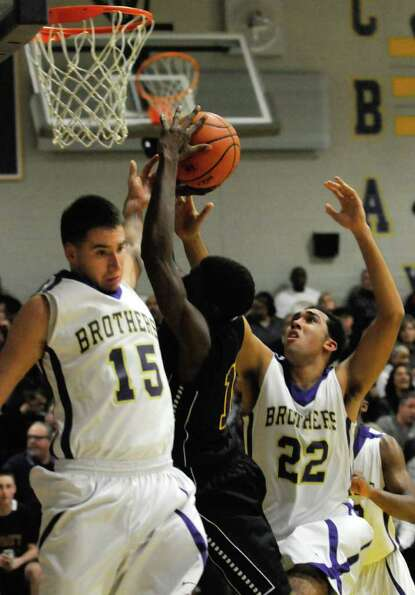 Troy's Trahmier Burrell trys to get through CBA defenders Joe Krong and Nate Robinson during their b