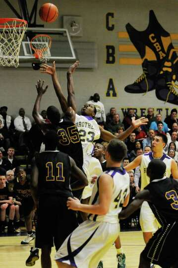 CBA's Sha Cancer puts a shot up over Troy's Kareem Brown during their boy's high school basketball m