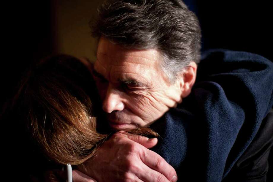 Republican presidential candidate Texas Gov. Rick Perry gets a hug from a supporter after making remarks on caucus night on Tuesday, Jan. 3, 2012, in West Des Moines, Iowa.  (AP Photo/Evan Vucci) Photo: Evan Vucci, Associated Press / AP