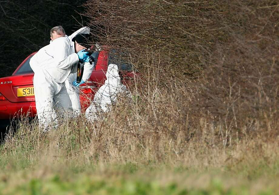 KING'S LYNN, ENGLAND - JANUARY 03:  A Police forensic scientist photographs evidence at the scene in woods on Kings Avenue where human remains were found on New Year's Day on January 3, 2012 in King's Lynn, England. Police have launched a murder investigation after the remains were found by a walker in woods at the village of Anmer adjacent to the Queen's Sandringham Estate.  (Photo by Christopher Furlong/Getty Images) Photo: Christopher Furlong, Getty Images