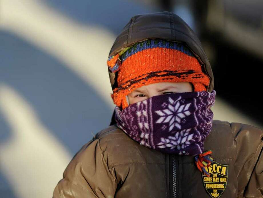 Noah Ratner, 2, peeks out from above his scarf as he walks with his mother, Michelle, on  Washington Avenue. Temperatures were in the single digits Wednesday morning in Albany  Jan. 4, 2011. (Skip Dickstein / Times Union) Photo: SKIP DICKSTEIN / 2011
