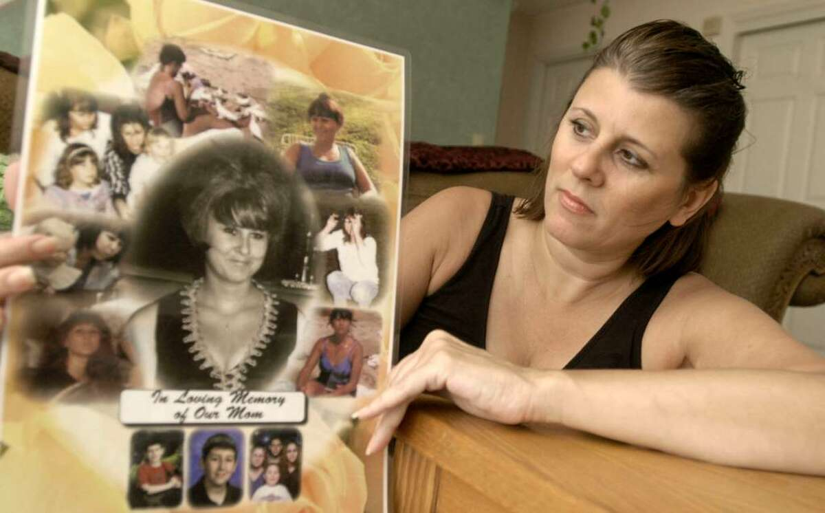 Sherrie Passaro, 46, of Danbury holds a poster of photographs in memory of her mother Mary Badaracco, who disappeared from her home 25 years ago this week. Photo taken August 19, 2009.