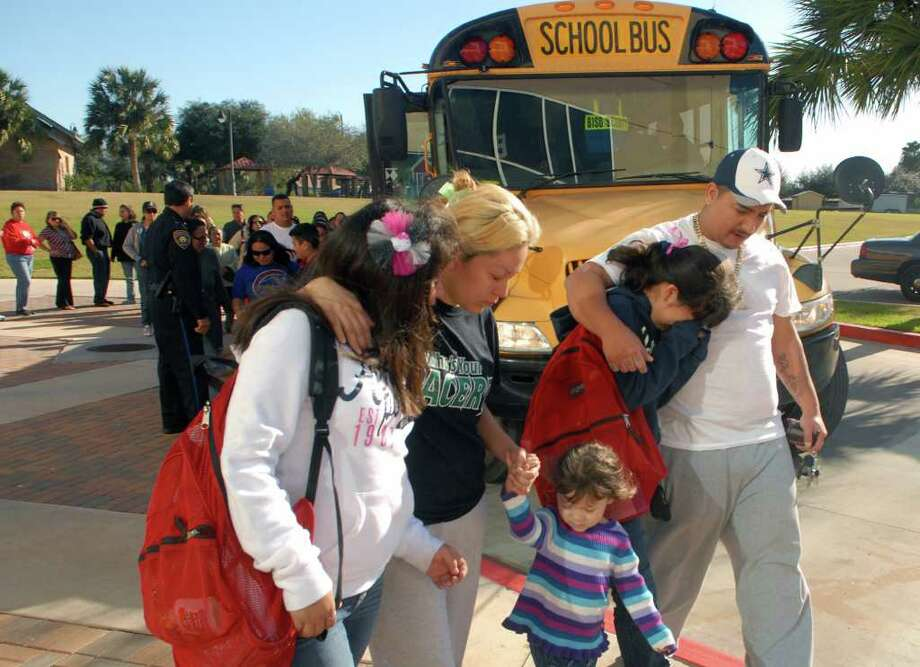 Nancy Blanco and husband Arturo Carreon comfort their children Ashley Carreon, 12, and Josey Lynn Carreon, 13, students at Cummings Middle School, after being reunited with them at a park across the street from the school. Photo: AP